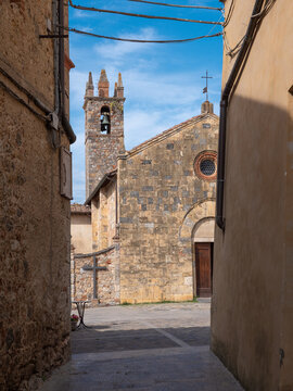 View from a Narrow Street in front of the Bell tower and the Church of Santa Maria Assunta in Piazza Roma in Monteriggioni, Siena - Italy