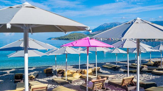 Girl on a sun lounger under one pink open beach umbrella among the rest of grays. Large beach umbrellas over sun loungers on pebble beach
