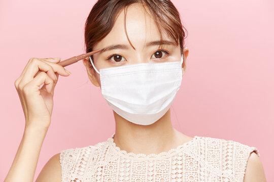 マスクをした若い女性のメイクアップイメージ