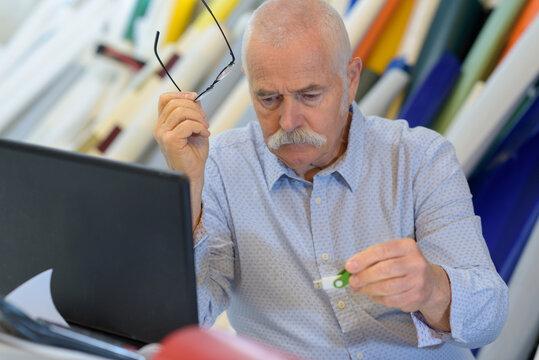 senior man laptop studio portrait concept