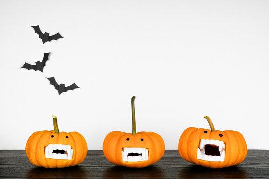 Fun Halloween pumpkins with vampire teeth on a black shelf against a white wall with bats. Copy space.