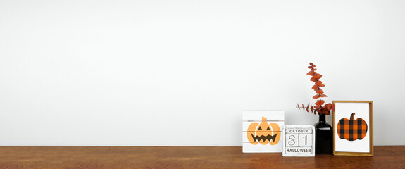 Obraz Halloween decor on a wood shelf. Shabby chic wood signs, calendar and orange branches against a white wall banner. Copy space. - fototapety do salonu
