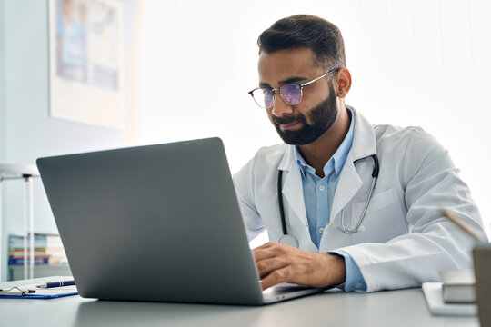 Indian male doctor medic expert wearing white coat using laptop computer at work in hospital, checking patients electronic files medical forms, having online virtual telehealth consultation.