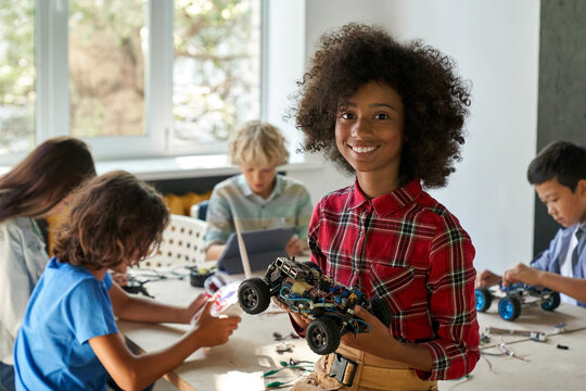 Happy African American junior school kid holding robotic car looking at camera at STEM class. Smiling black child preteen girl posing with robot vehicle. Portrait. Engineering and coding education.