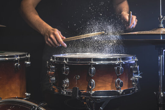 The drummer plays the snare drum with splashing water.