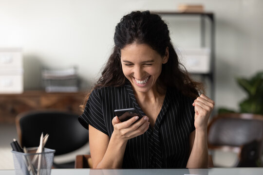 Happy millennial Latin woman in casual excited with good news, using smartphone, looking at screen, making winner yes gesture. Businesswoman reading text message, celebrating win, high result