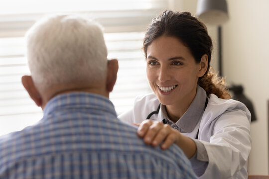 Happy optimistic female GP doctor giving hope and support to senior 80s male patient at appointment, touching shoulder of man, smiling, telling good news. Successful therapy, geriatric healthcare