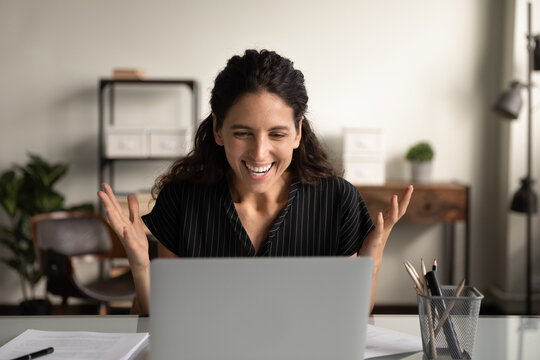 Happy excited businesswoman surprised and overjoyed with good news, celebrating win, success, achieve, high job result, getting promotion, winning prize, looking at screen, making winner gesture