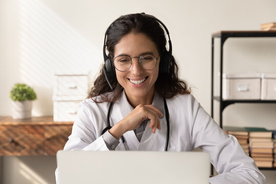 Happy friendly female physician in headphones chatting to patient on video call, giving help, online consultation, advice, attending virtual medical conference, webinar on laptop, using computer