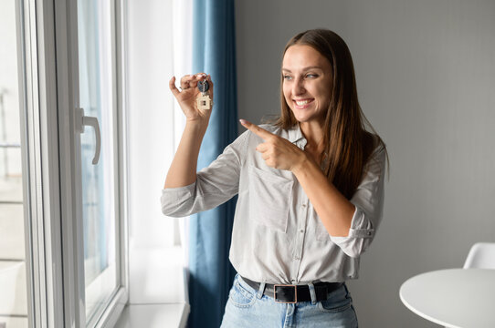 Relocation concept. Headshot of excited caucaian female moving in new home or apartment. Cheerful woman homeowner looking at camera and points finger at the keys with keychain in her hand