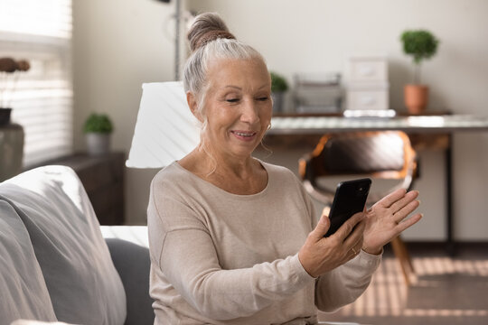 Happy elderly grey haired lady using smartphone at home, making video call, talking to family, relatives online. Senior patient consulting doctor at virtual meeting on mobile phone, smiling at screen