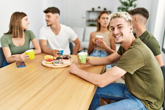 Group of young friends smiling happy having breakfast sitting on the table at home.