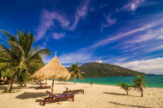 Wooden beach bench on white sand beach with coconut palm tree summer vacation