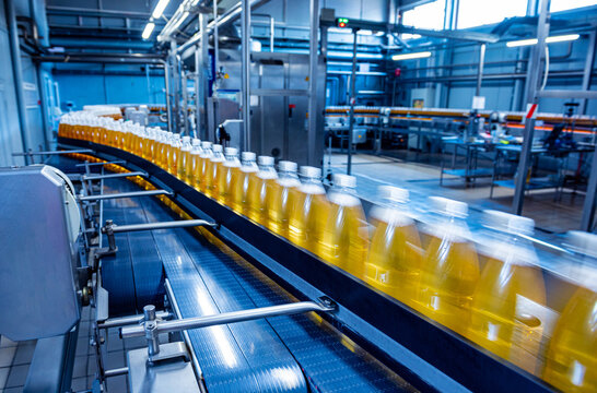 Conveyor belt with bottles for juice or water at a modern beverage plant