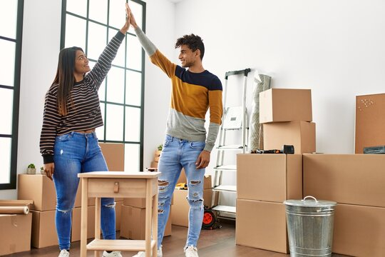 Young latin couple smiling happy assembling piece of furniture at new home.