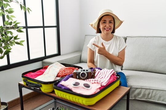 Beautiful middle age hispanic woman packing summer clothes in suitcase cheerful with a smile of face pointing with hand and finger up to the side with happy and natural expression on face