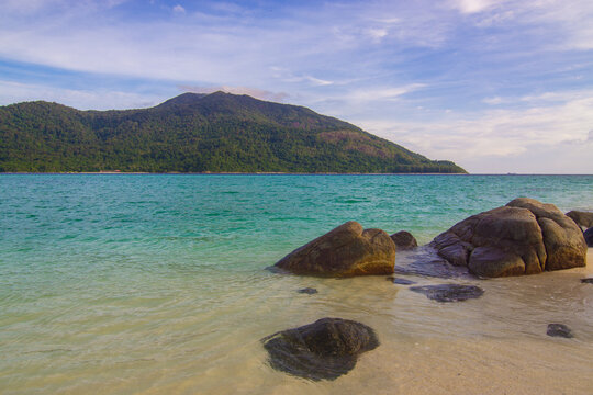 Tropical white sand beach o n island with mountain sea view