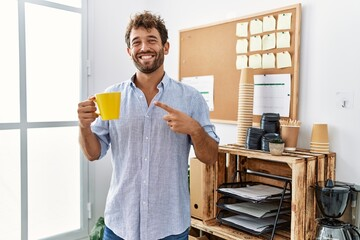 Young handsome man drinking a cup coffee at the office smiling happy pointing with hand and finger