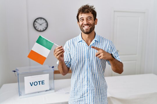 Young handsome man at political campaign election holding ireland flag smiling happy pointing with hand and finger