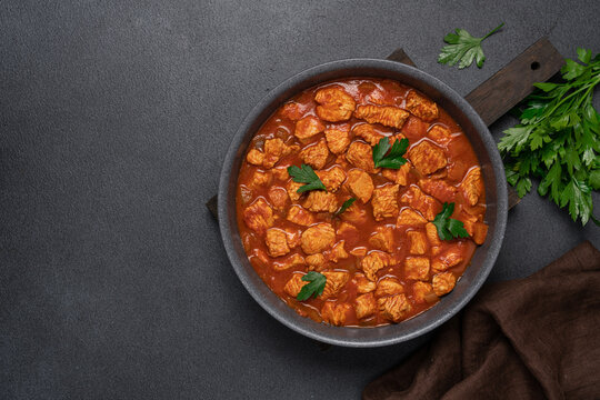 Stew turkey or chicken meat in tomato sauce. Meat dish in frying pan on black background