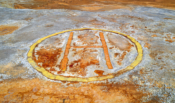 Old corroded helipad at abandoned mine, industrial background with spots of rust over grey rough surface