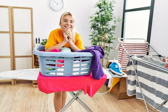 Young blonde girl smiling happy leaning on basket with clean clothes at home.