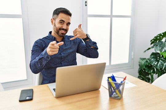 Young hispanic man with beard working at the office with laptop smiling doing talking on the telephone gesture and pointing to you. call me.