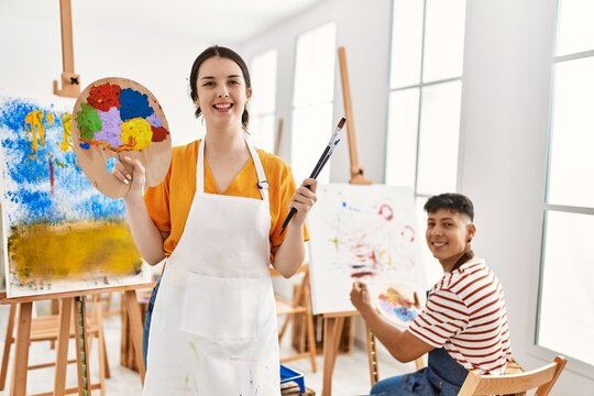 Two hispanic paint students smiling happy painting at art studio. Woman holding palette and paintbrush.