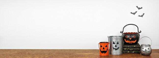 Halloween decor on a wood shelf. Rustic metal jack o lantern candle holders against a white wall...
