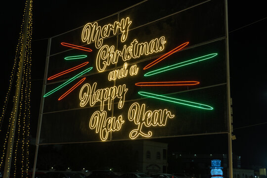 Christmas lights outside with sign for Merry Christmas and Happy New Year for winter xmas festive themes