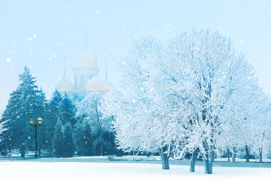 Snowfall in the city park. Winter Russian landscape. Snowy trees and a church in the background.