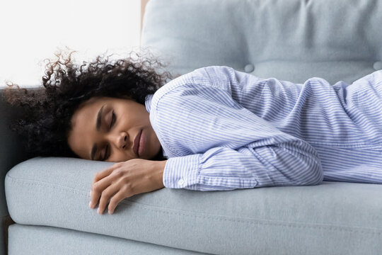 Difficult day. Too tired millennial african american woman lie on couch with closed eyes fall asleep exhausted with hard work insomnia sleepless night. Young mixed race female relax sleep nap on sofa