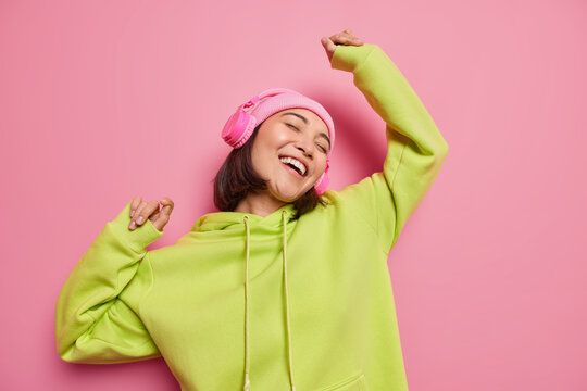 Upbeat teenage girl chills indoor while listening music enjoys good sound in new headphones dances catches every bit enjoys free time wears hat green hoodie isolated over pink studio background