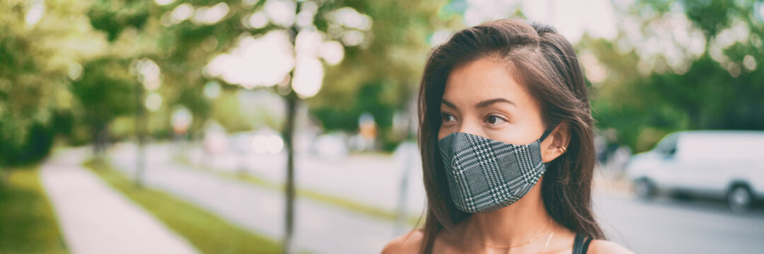 Asian woman walking outside wearing stylish fashion cloth face mask in plaid pattern. Serious young ethnic model portrait banner panoramic.