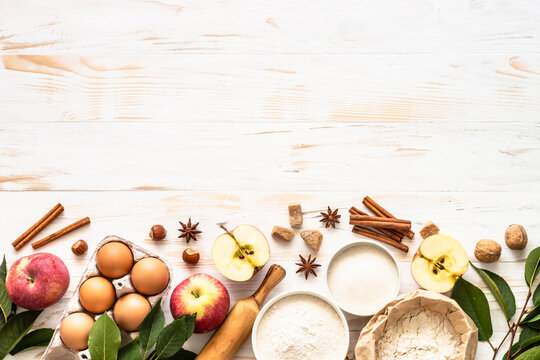 Ingredients for cooking autumn baking. Flour, sugar, eggs, apples and spices at white wooden table. Top view with space for design.
