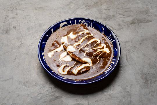 Mexican food. Enchiladas with mole sauce also called Enmoladas on grey background