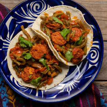 Mexican food. Chorizo and nopales tacos on wooden background