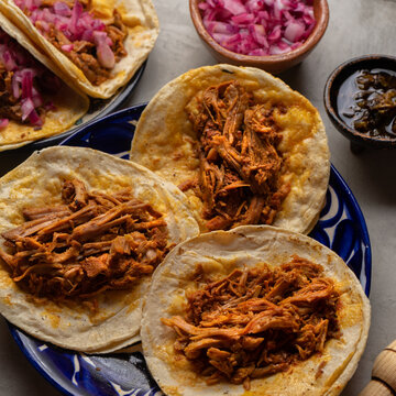 Mexican food. Pork tacos called Cochinita pibil on grey background