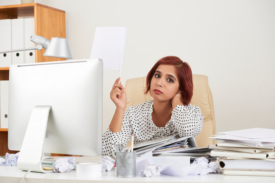 Tired hopeless pretty young businesswoman leaning on stack of documents and lifting hand with white flag