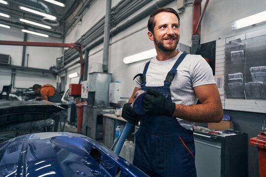 Male car workshop worker taking care of sander after work