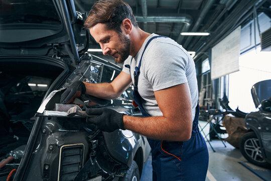 Pleased automotive repairman flattening component part of car