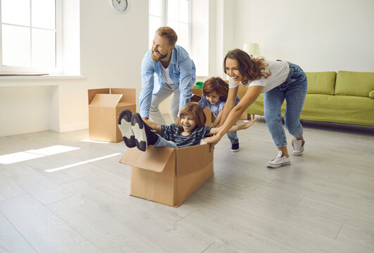 Happy family having fun in new home. Joyful excited first-time buyers with children playing with cardboard boxes in living room interior. Real estate, residential mortgage, buying dream house concept