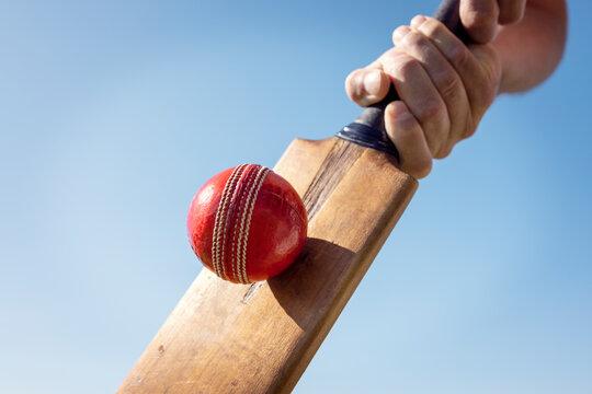 Cricket player batsman hitting a ball with a bat shot from below background
