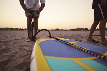 Close up of man prepares to paddle surf on a beach inflating sup board