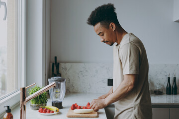 Side view young serious single african american man 20s wearing casual clothes prepare sweet salad...