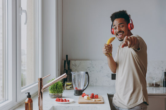 Young african american man in casual clothes headphones listen music sing song in banana microphone point finger camera preparing cook food in indoor kitchen at home alone. Healthy lifestyle concept