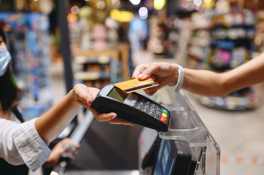 Cropped close up woman hand arm shopping at supermaket put credit card to wireless modern bank payment terminal process acquire payments near cashier checkout inside store. People purchasing concept.