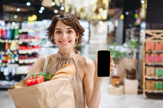 Young woman 20s in casual clothes shopping at supermaket store with craft paper package with groceries show mobile cell phone blank screen workspace area inside hypermarket. Gastronomy food concept