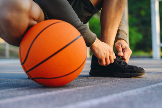 Cropped close up young caucasian sportsman man 20s wear grey sportswear hood training sit laces up black sneakers shoes with ball at basketball game playground court Outdoor courtyard sports concept