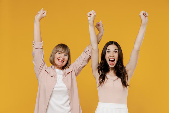 Two young happy daughter mother together couple women in casual beige clothes do winner gesture clench fist raise hands isolated on plain yellow background studio portrait Family lifestyle concept.